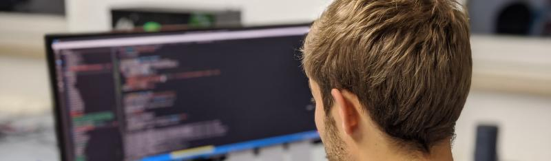 A person in looking at code on a computer screen